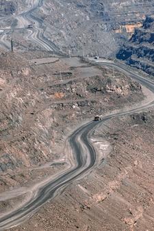 L'autocarro con cassone ribaltabile della cava di minerale di ferro si muove sulla strada di terreni terrazzati a gradini, industria mineraria, attrezzature minerarie e estrattive.