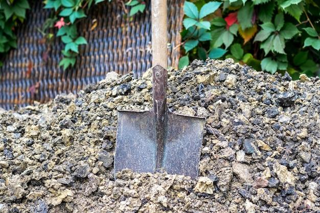 Una pala di ferro è conficcata nel terreno. scavare fosse e trincee