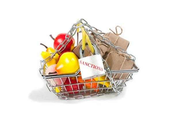 Un cestino del supermercato in ferro pieno di spesa, frutta, scatole con fiocchi, riavvolgimento della catena e con un lucchetto con la scritta sanzioni, su fondo bianco