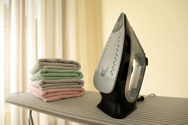 Asse da stiro con ferro e pile di asciugamani