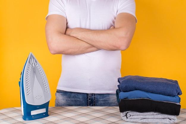 Concetto di vestiti da stiro. foto ritagliata di un uomo in piedi davanti all'asse da stiro con un ferro da stiro e vestiti piegati su di esso isolati su sfondo giallo