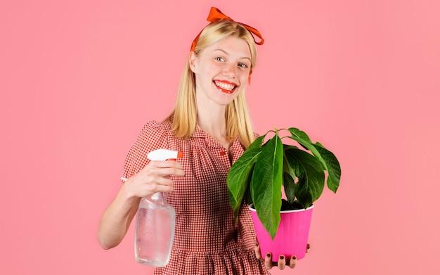 Irrigazione. concetto di irrigazione. donna con flacone spray che spruzza piante d'appartamento. la ragazza si prende cura del fiore.