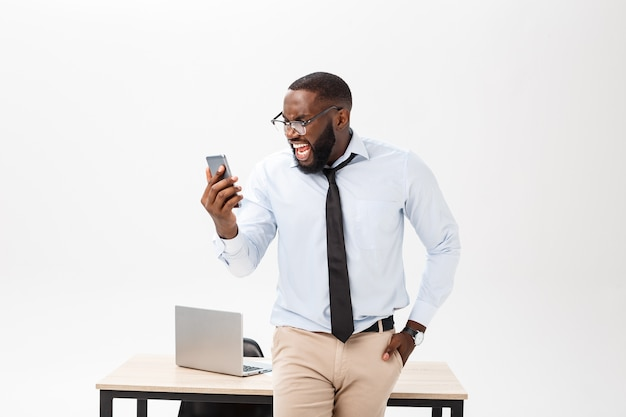 Il giovane imprenditore maschio dalla pelle scura irritato che si trova sul posto di lavoro si sente molto stressato e arrabbiato