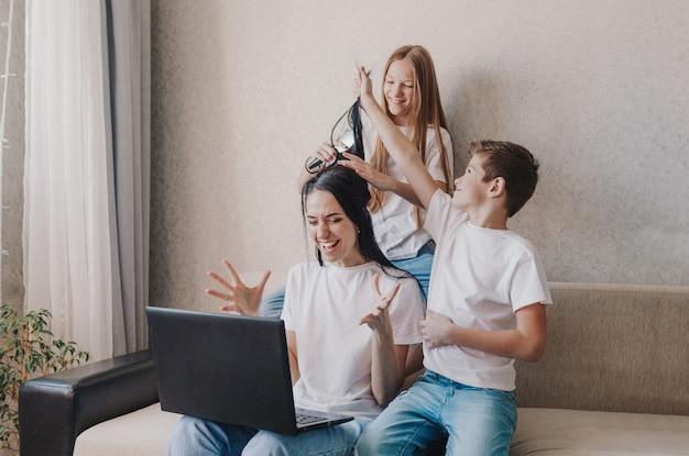 Una madre irritata si siede sul divano e lavora a casa su un laptop, i bambini attivi giocano con i capelli della madre, si pettinano