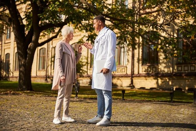 Donna anziana irritata in disaccordo con il suo medico calmo nel mezzo di un marciapiede