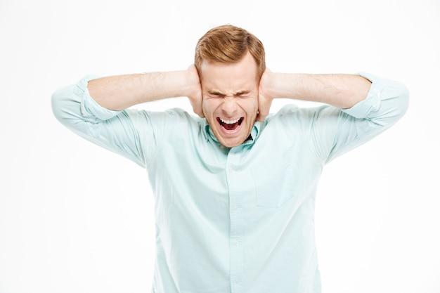 Il giovane stressato irritato ha coperto le orecchie con le mani e gridava sul muro bianco
