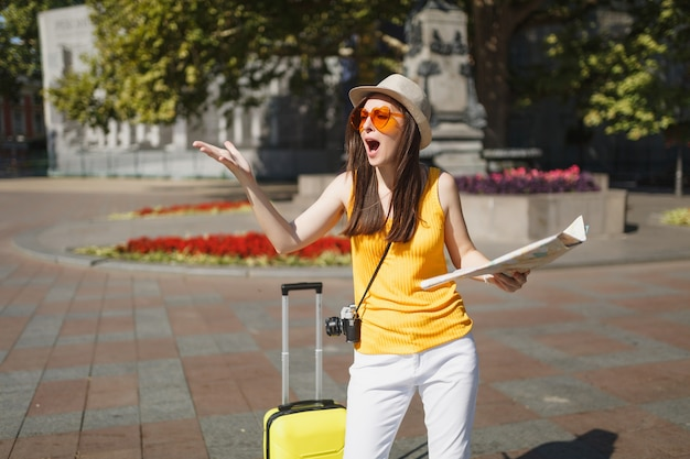 Turista viaggiatore irritato con occhiali a cuore arancione con valigia che tiene la mappa della città allargando le mani in città all'aperto. ragazza che viaggia all'estero per viaggiare nel fine settimana. stile di vita del viaggio turistico.