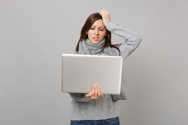Giovane donna irritata in maglione grigio, sciarpa che mette mano sulla testa, lavorando su computer pc portatile isolato su sfondo grigio muro. stile di vita sano, consulenza sul trattamento online, concetto di stagione fredda.