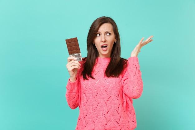 Giovane donna irritata in maglione rosa lavorato a maglia che guarda in alto, allarga le mani, tiene la barretta di cioccolato isolata su sfondo blu turchese muro, ritratto in studio. concetto di stile di vita della gente. mock up copia spazio.