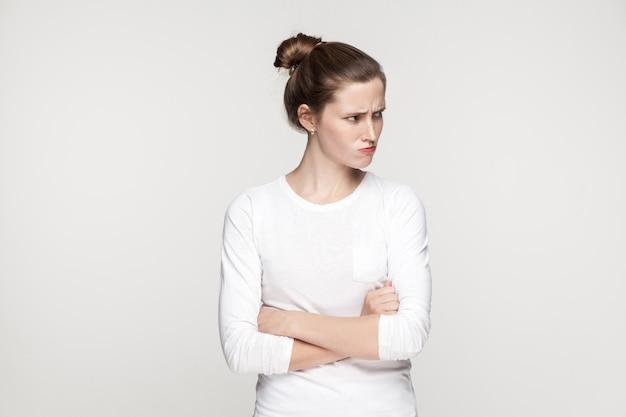 Ragazza di irritazione. la giovane donna adulta ha attraversato le mani e distoglie lo sguardo. ripresa in interni