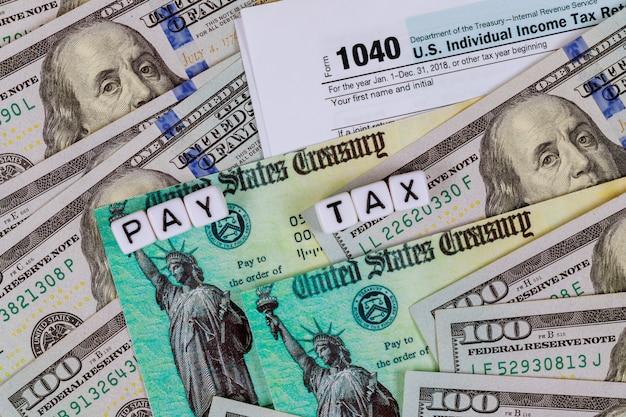 Modulo di dichiarazione dei redditi irs 1040 con banconote in dollari statunitensi in valuta