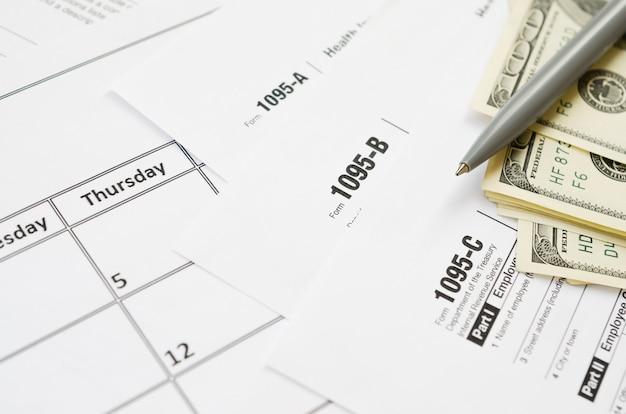 Il modulo irs 1095-a 1095-b e 1095-c si trova sulla pagina vuota del calendario con penna e banconote da un dollaro