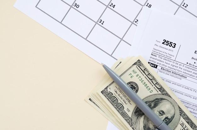 Modulo irs 2553 l'elezione di un vuoto fiscale della small business corporation si trova con la penna e molte centinaia di banconote in dollari sulla pagina del calendario