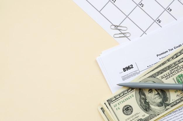 Modulo irs 8962 premio fiscale cerdit ptc vuoto con penna e banconote da centinaia di dollari sulla pagina del calendario