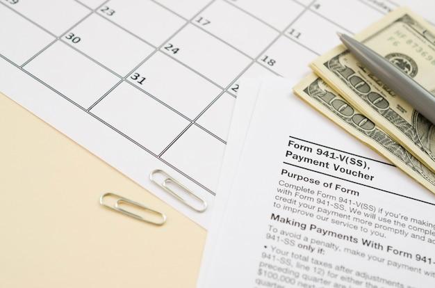 Il modulo voucher irs 941-v vuoto si trova con la penna e molte centinaia di banconote in dollari sulla pagina del calendario