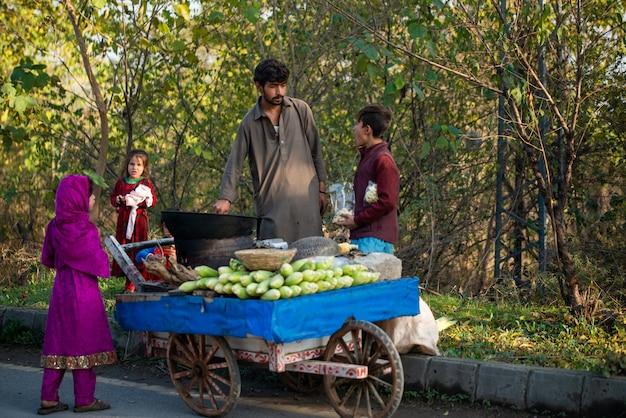 Islamabad, islamabad capital territory, pakistan - 2 febbraio 2020, i giovani ragazzi stanno arrostendo mais fresco per i clienti.
