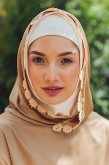 Bella donna islamica in un vestito musulmano che sta sugli alberi di autunno della foresta del fondo della strada del parco di estate