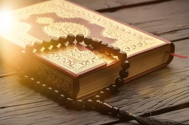 Libro islamico corano con rosario sullo sfondo