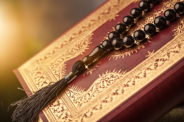 Libro islamico corano con rosario su sfondo grigio