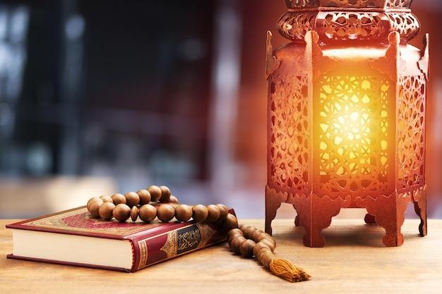 Corano del libro sacro islamico con grani del rosario e lanterna araba ornamentale