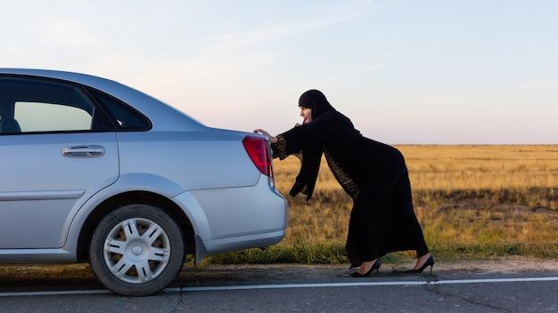 Una donna islamica sta spingendo un'auto lungo la strada