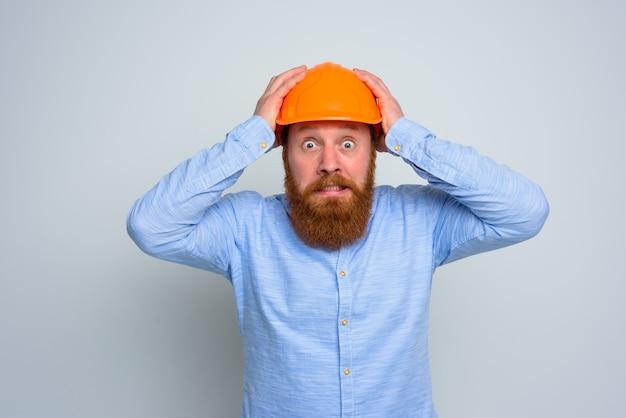 Architetto impaurito isolato con barba e casco arancione