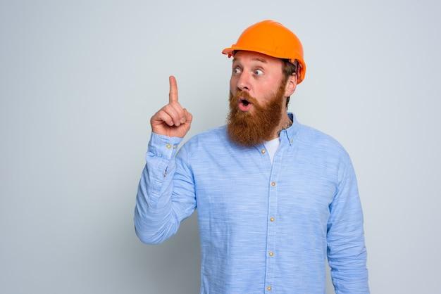 Architetto stupito isolato con barba e casco arancione