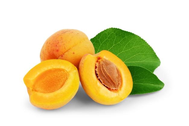Albicocche isolate frutta intera di albicocca fresca con foglia e metà