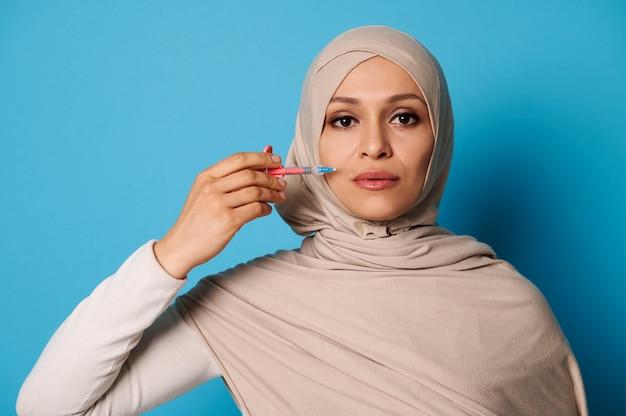 Ritratto isolato di bellezza di una giovane donna musulmana araba che tiene una siringa vicino al suo fronte.