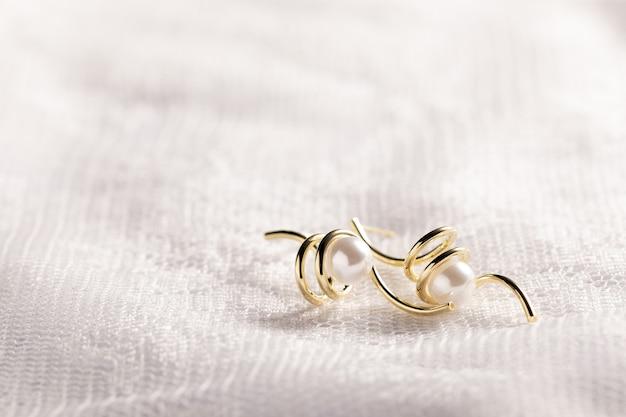 Primo piano isolato di accessori di perle d'oro su uno sfondo di pizzo bianco