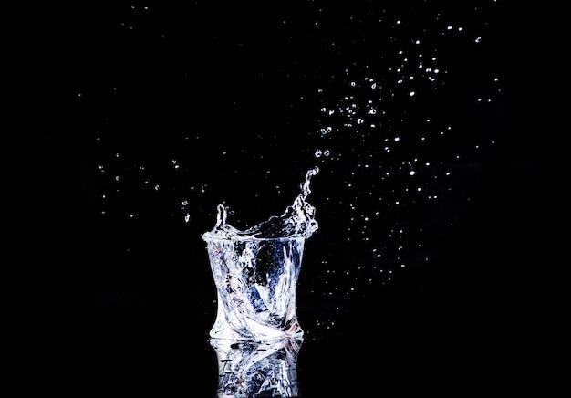 Acqua fredda isolata in un bicchiere con schizzi e cubetti di ghiaccio su sfondo nero
