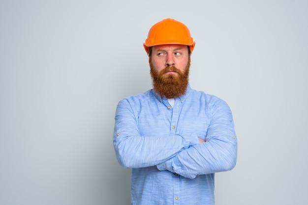 Architetto dubbioso isolato con barba e casco arancione