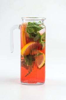 Brocca di vetro isolata di limonata alla frutta rossa