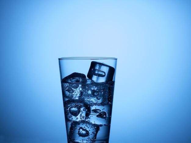 Bicchiere d'acqua isolato con cubetti di ghiaccio su sfondo azzurro