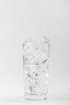 Bicchiere d'acqua isolato con ghiaccio