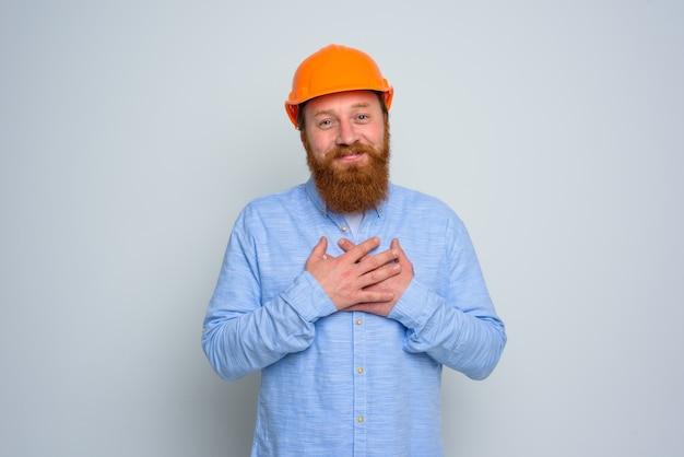 Architetto felice isolato con barba e casco arancione