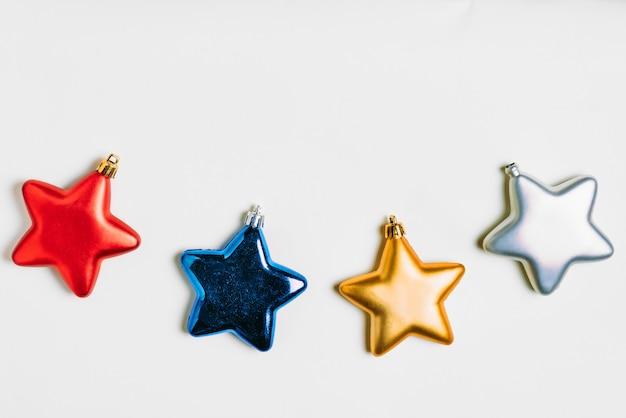 Isolato molti colori di stelle metalliche come rosso, blu, oro e argento per natale.