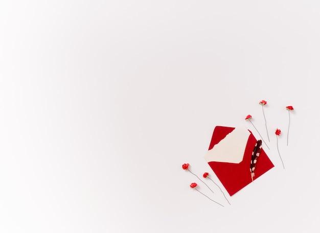 Rose rosse di carta isolate e busta con piuma su uno sfondo bianco con spazio di copia