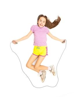 Foto isolata di una ragazza attiva carina che salta con la corda per saltare