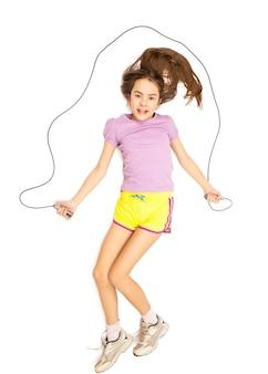 Foto isolata di una ragazza sorridente carina che salta con la corda per saltare