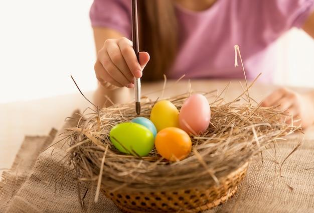 Foto isolata della ragazza che dipinge le uova di pasqua easter