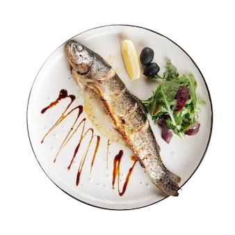 Piatto isolato di pesce alla griglia gourmet con insalata