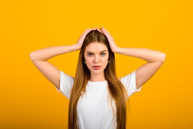 Il ritratto isolato della donna felice ha un sorriso a trentadue denti, chiude gli occhi, prova piacere dai complimenti, si leva in piedi sopra il muro giallo. concetto di emozioni e sentimenti positivi