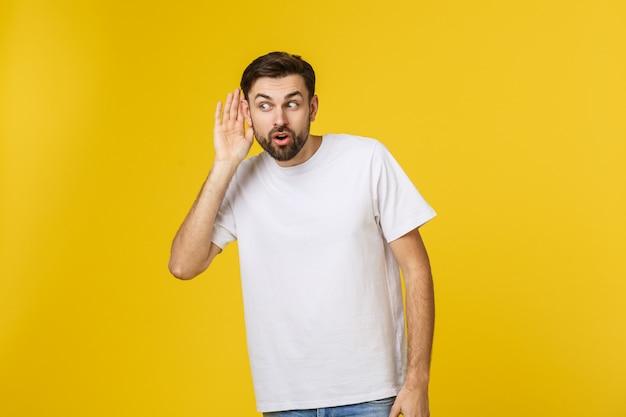 Ritratto isolato del giovane sorridente in abbigliamento casual che ascolta attentamente con la sua palma vicino all'orecchio concetto di curiosità e di intercettazione