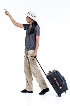 Isolato ritratto studio colpo di asiatico felice capelli lunghi coda di cavallo viaggiatore avventura maschio indossa cappello secchio in piedi guardare fotocamera tirare carrello in tessuto bagagli da viaggio per le vacanze su sfondo bianco.