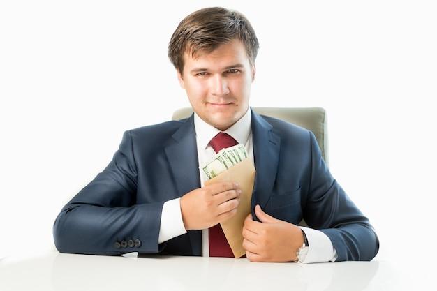 Ritratto isolato di un politico venale che mette soldi in una busta nella tasca della sua tuta