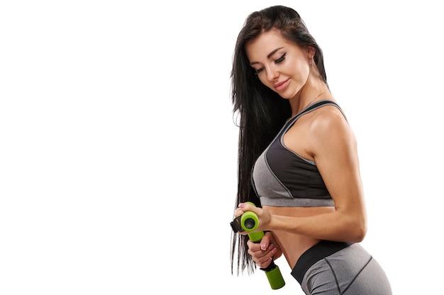 Ritratto isolato su uno sfondo bianco di una bella ragazza bodybuilder, eseguendo esercizio con manubri