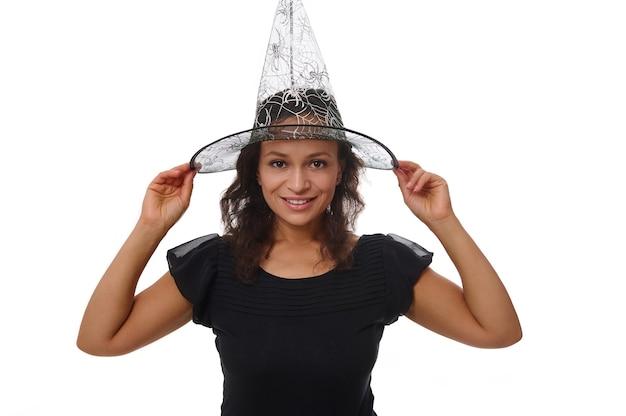 Ritratto isolato su sfondo bianco con copia spazio per l'annuncio di halloween di una bella donna sorridente con un bel sorriso a trentadue denti, che indossa un cappello da mago strega e guarda la fotocamera