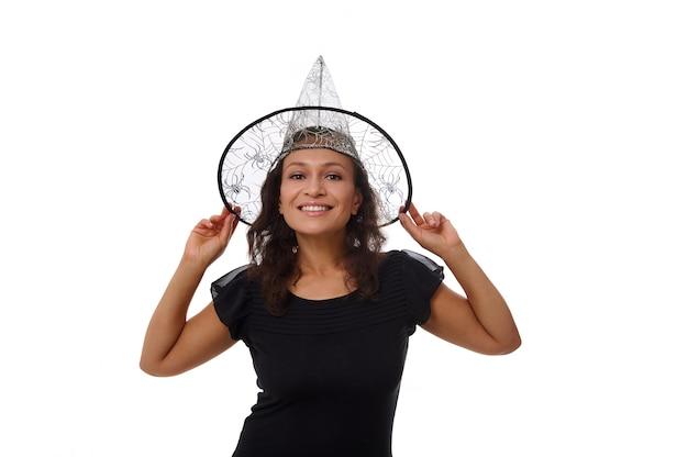 Ritratto isolato su sfondo bianco con copia spazio per la pubblicità di halloween di una giovane donna attraente che sorride con un bel sorriso a trentadue denti, indossa un cappello da mago strega e guarda la fotocamera