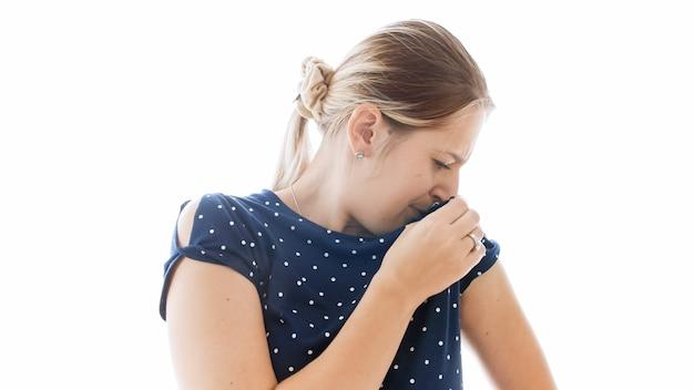 Ritratto isolato di giovane donna che odora le sue ascelle puzzolenti sudate.